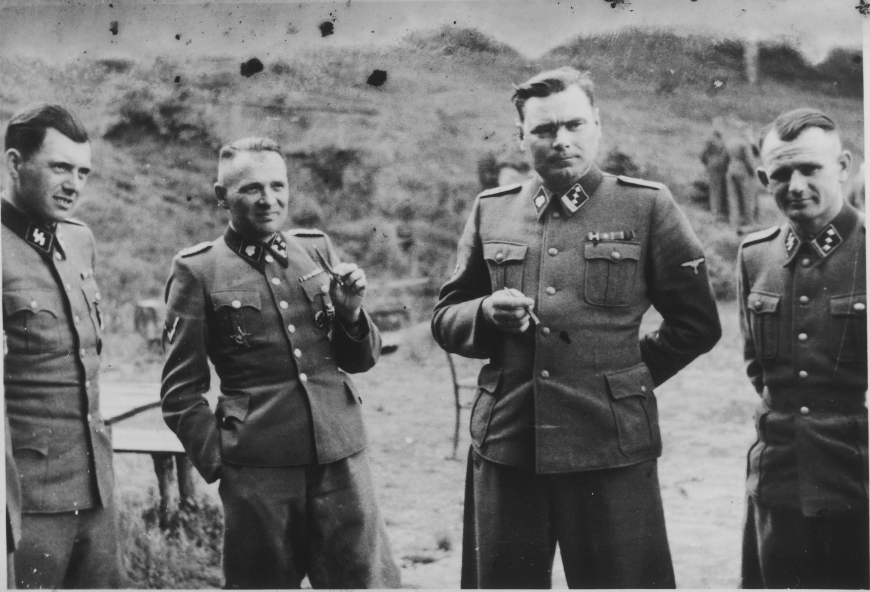 SS officers socialize on the grounds of the SS retreat Solahuette outside of Auschwitz.   From left to right they are: Dr. Josef Mengele, Rudolf Hoess (former Commandant of Auschwitz), Josef Kramer (Commandant of Birkenau) and Anton Thumann.   [Based on the officers visiting Solahutte, we surmise that the photographs were taken to honor Rudolf Hoess who completed his tenure as garrison senior on July 29.]