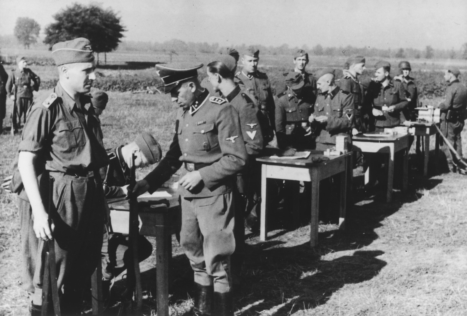 "SS officers gather for shooting practice. On the far left is Karl Hoecker.  The original caption reads ""Auf dem Schiessstand"" (at the firing range)."