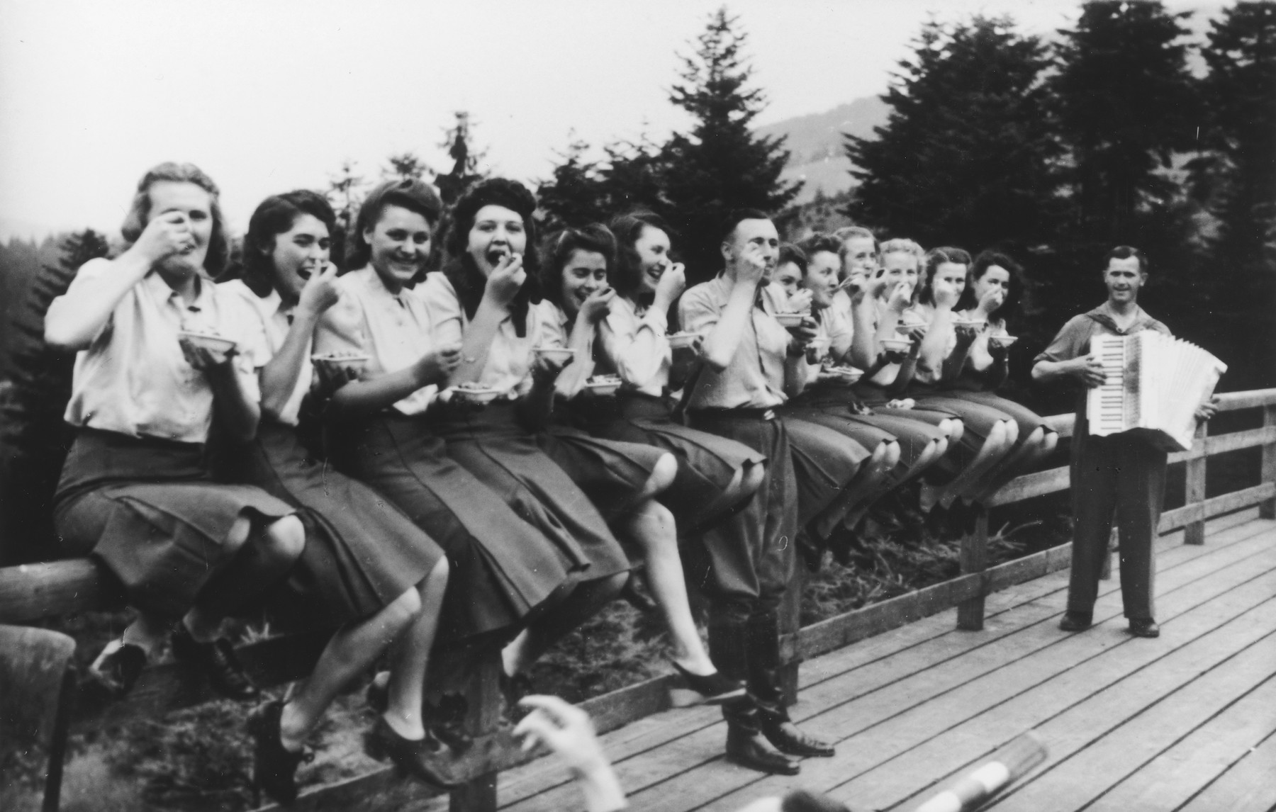 """Members of the SS Helferinnen (female auxiliaries) and SS officer Karl Hoecker sit on a fence railing in Solahuette eating bowls of blueberries.  In the background is a man playing the accordion.   The original caption reads """"Hier gibt es Blaubeeren"""" (there are blueberries here)."""