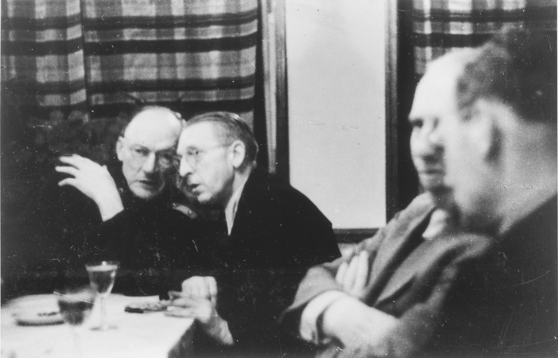Four Germans chat amongst themselves around a table in a hunting lodge.   Heinrich Josten is pictured on the left.