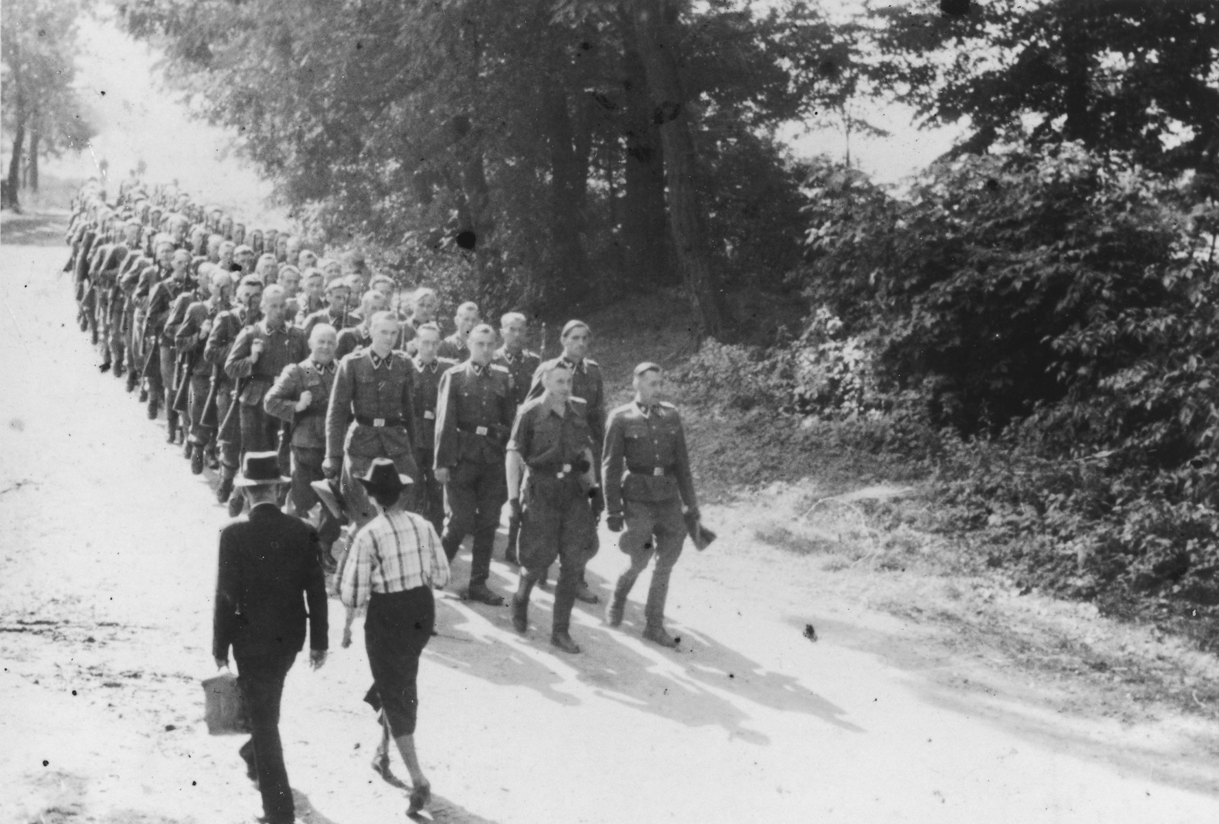 "SS officers and enlisted men march to shooting practice. Two civilians walk in the opposite direction.  The original caption reads ""Mit den Kdtr.-Stab auf dem Marsch zum Schiessstand"" (on the march with the commandant's office staff to the firing range)."
