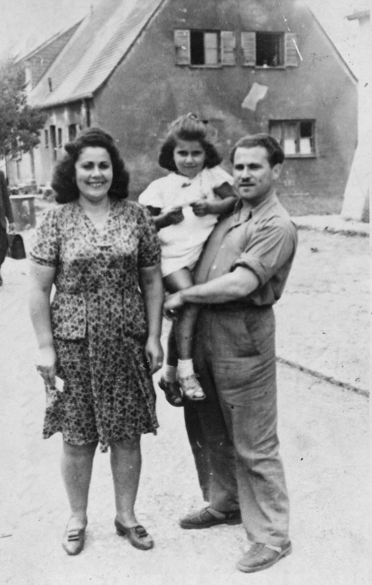 "Portrait of a Jewish couple and their daughter standing in front of a home in Thorn (Torun).  Pictured are Genia and Chil Heniek Szabason.  The caption reads ""To my dear cousin on the day we left Thorn, from Heniek."""