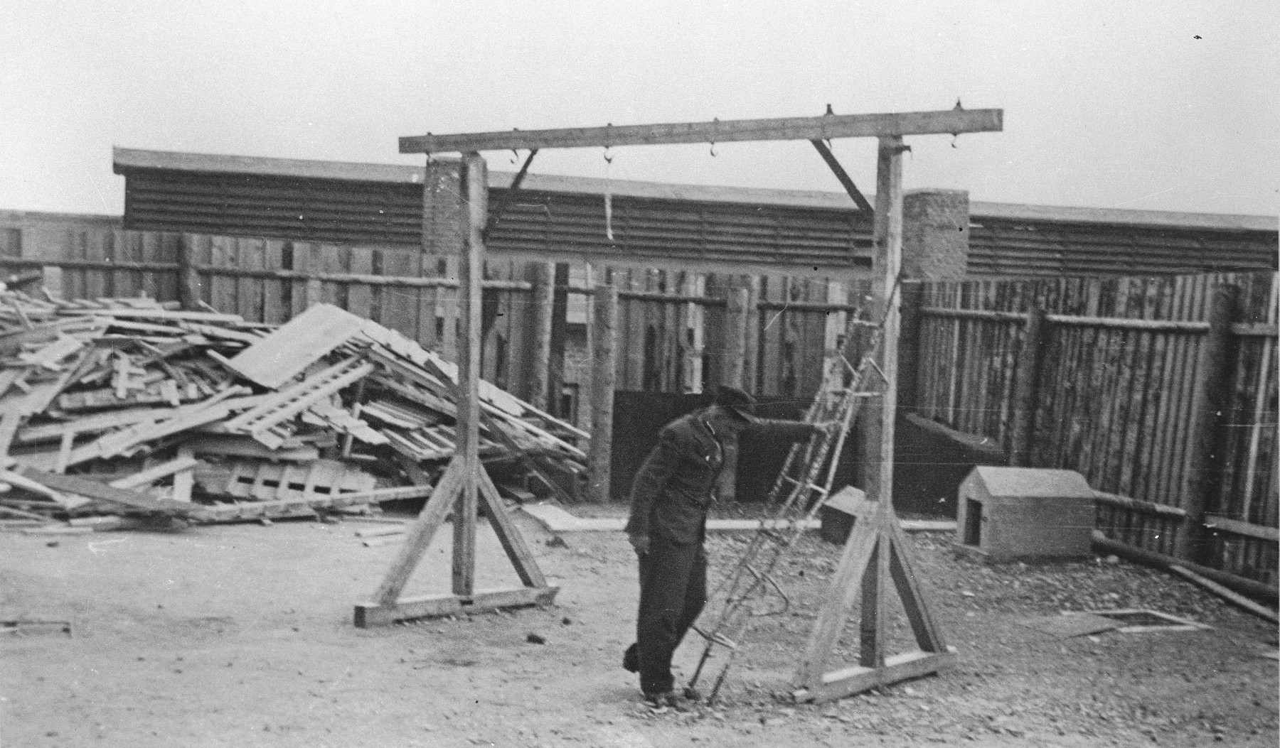 A former prisoner poses next to the gallows in the newly liberated Buchenwald concentration camp.