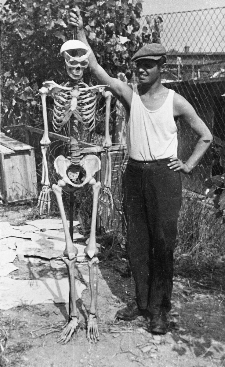 A young man poses with a human skeleton after the liberation of Buchenwald.