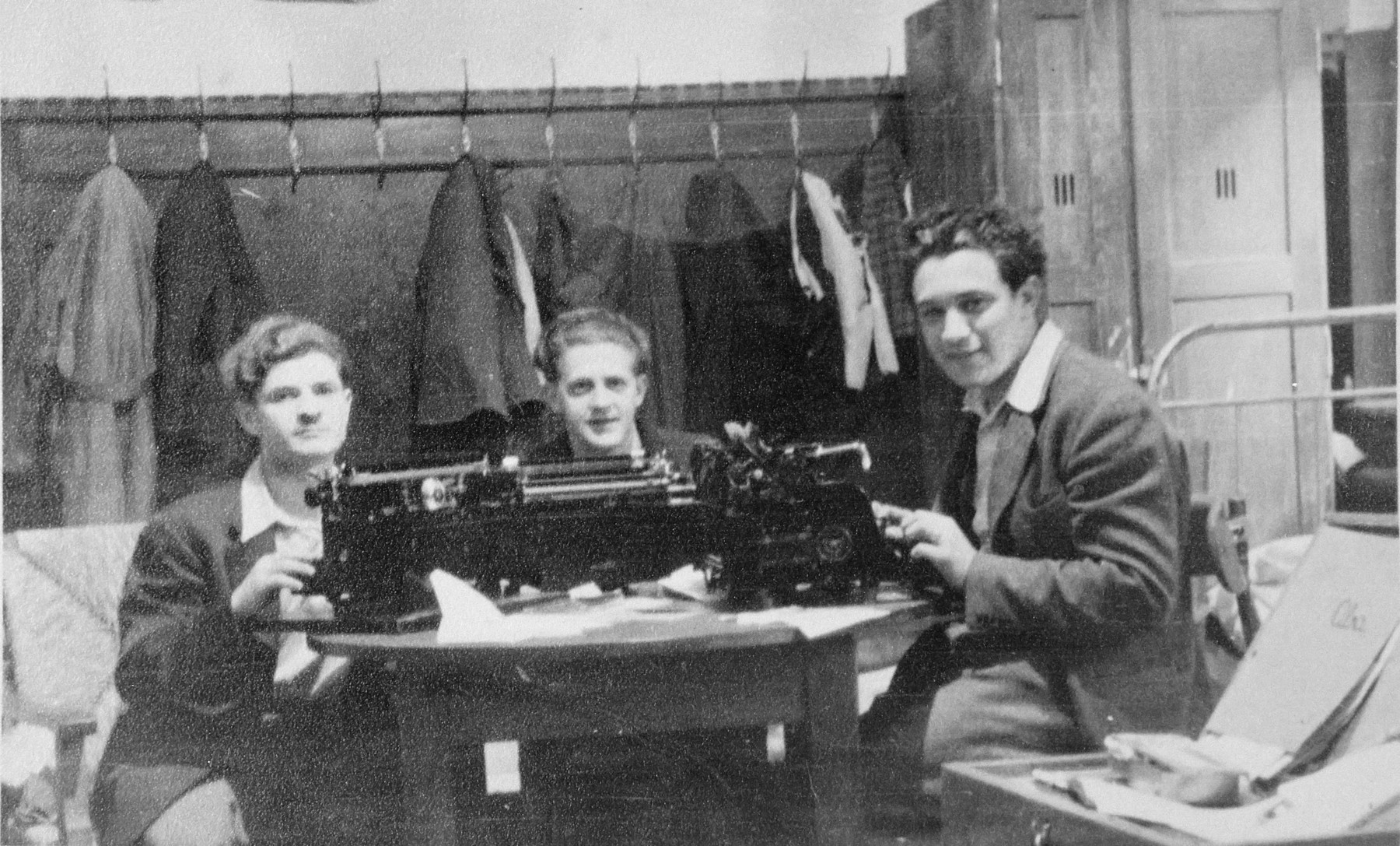 Three mebers of the Bricha type out documents to use in crossing Jews illegally from Austria to Germany.  They are working in Camp Mulln 6 in Salzburg.  Seated in the center is Aba Gefen (Weinstein).