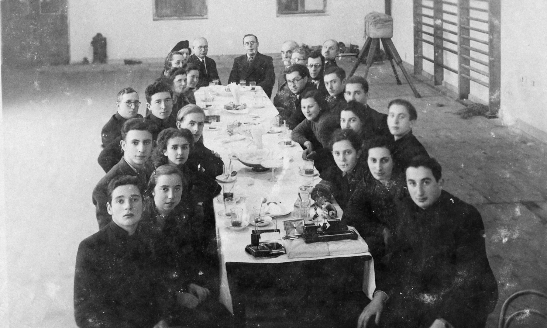 Students in their last year of a high school in Marijampole sit around a table set with glasses.  Aba Weinstein is seated fifth in the left row.