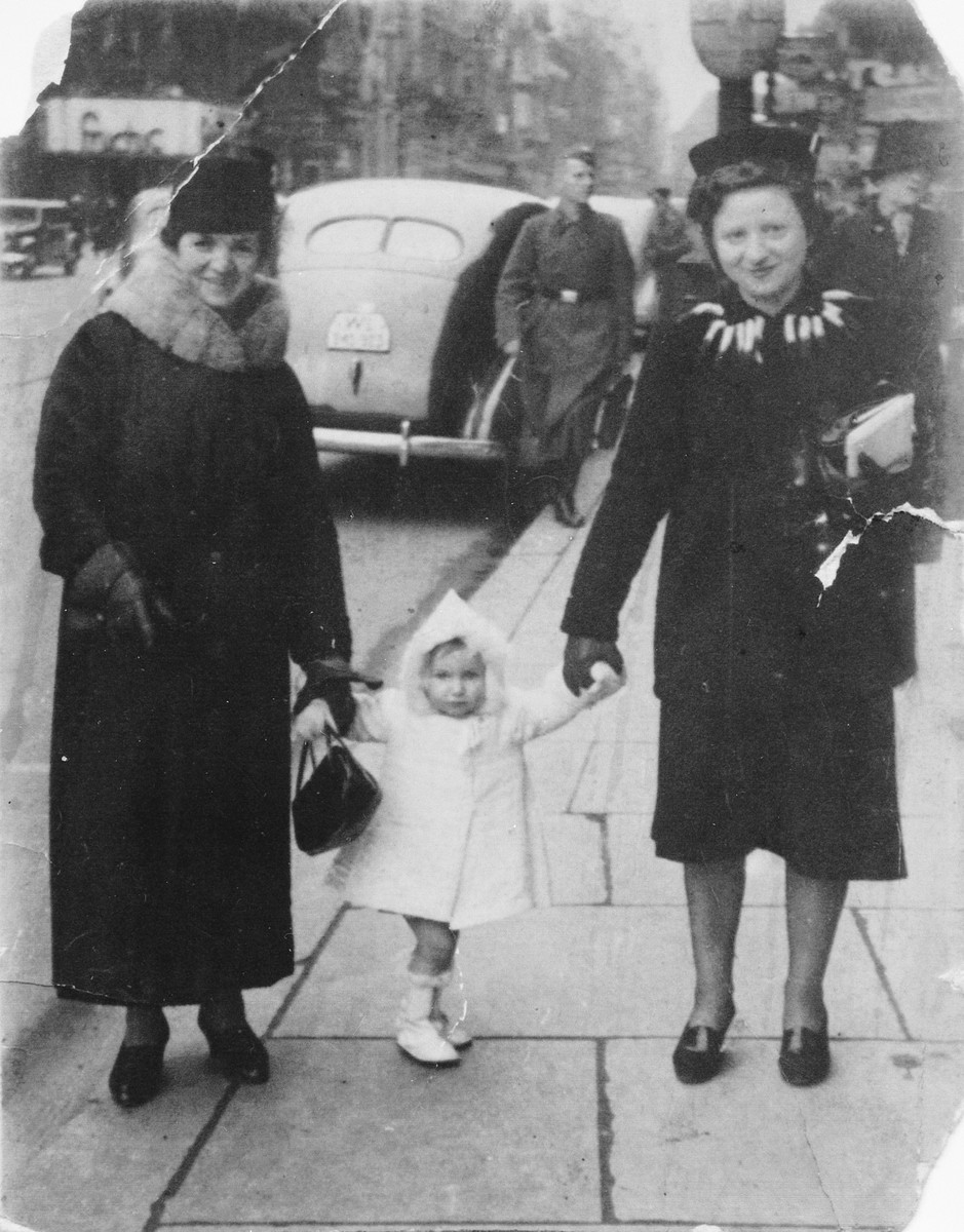 Three generations of a Jewish family walks down the street hand in hand.  Pictured are Fajga Aizenberg (right), her mother, and Fanny's  daughter, Josiane.