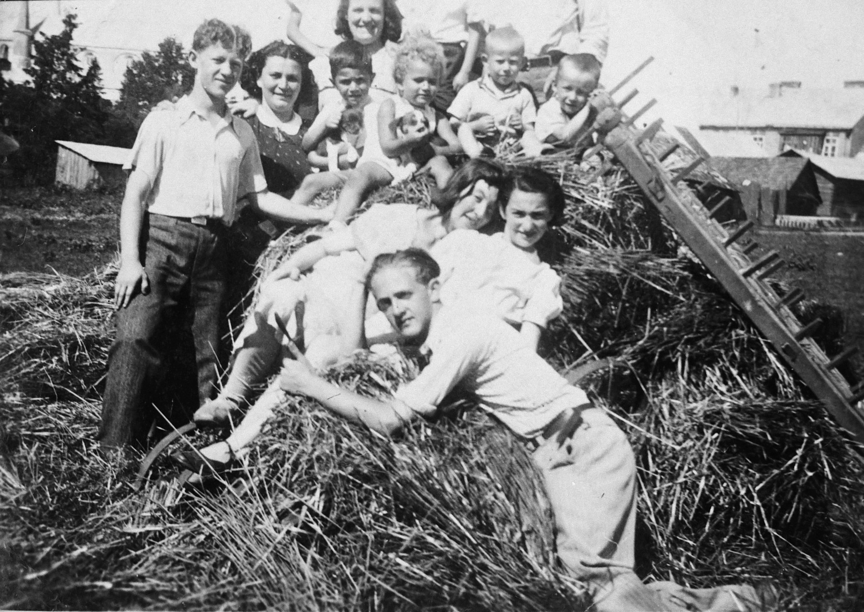 The children of an extended Lithuanian Jewish family poses on top of a haystack.  Standing on the far left is Benjamin Weinstein.  In front is his older brother Aba.