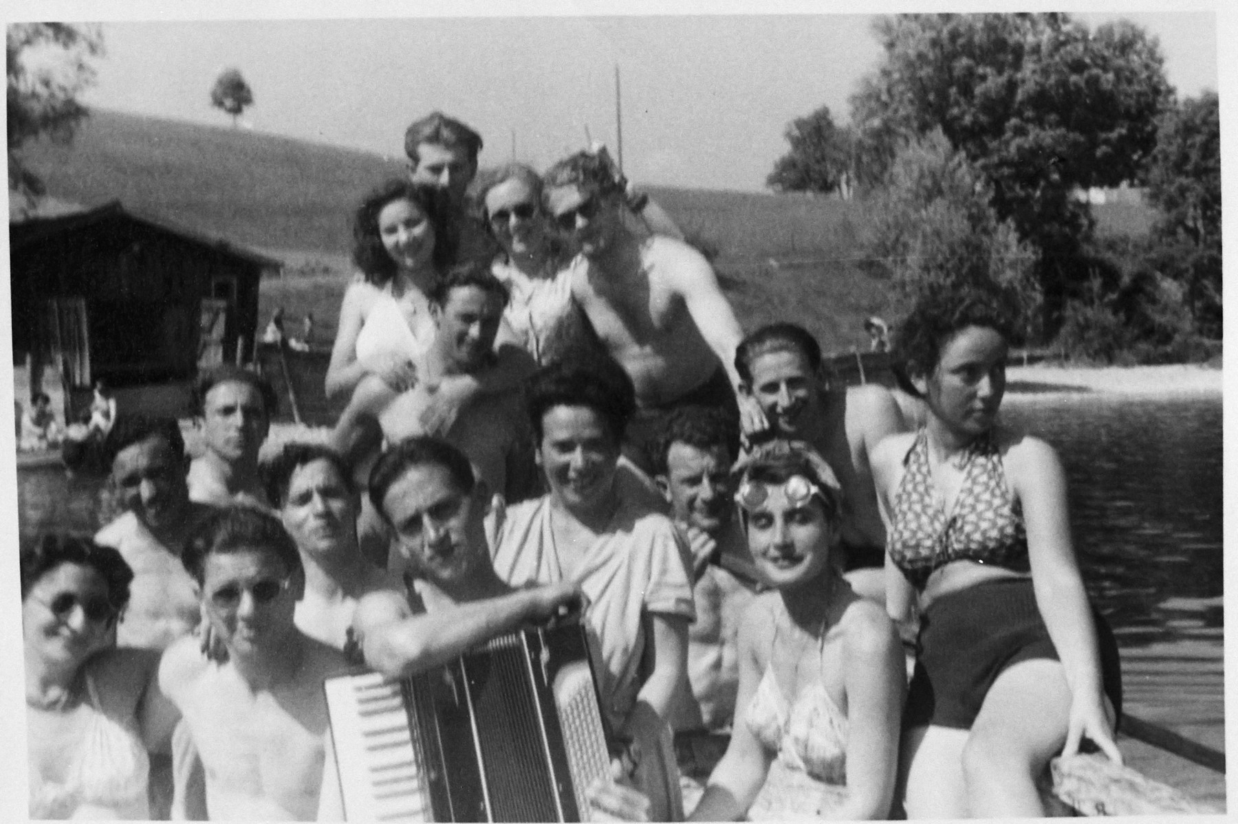 A group or Bricha activitists gathers by the shore of a lake or river in their bathing suits.  One is playing the accordian.  Among those pictured is Aba Gefen, top row, far right.