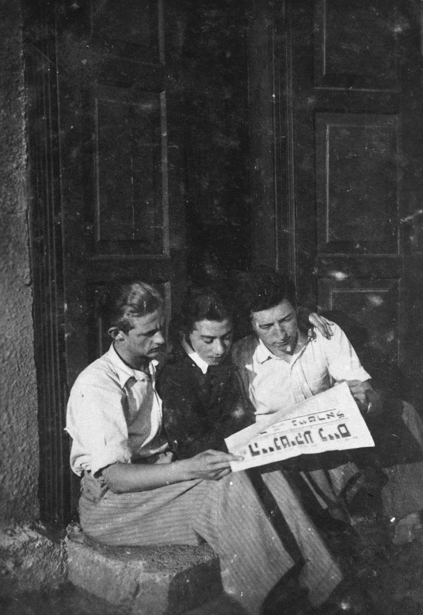 Three Jewish youth share a daily Yiddish newspaper.  Aba Weinstein is pictured on the far left.
