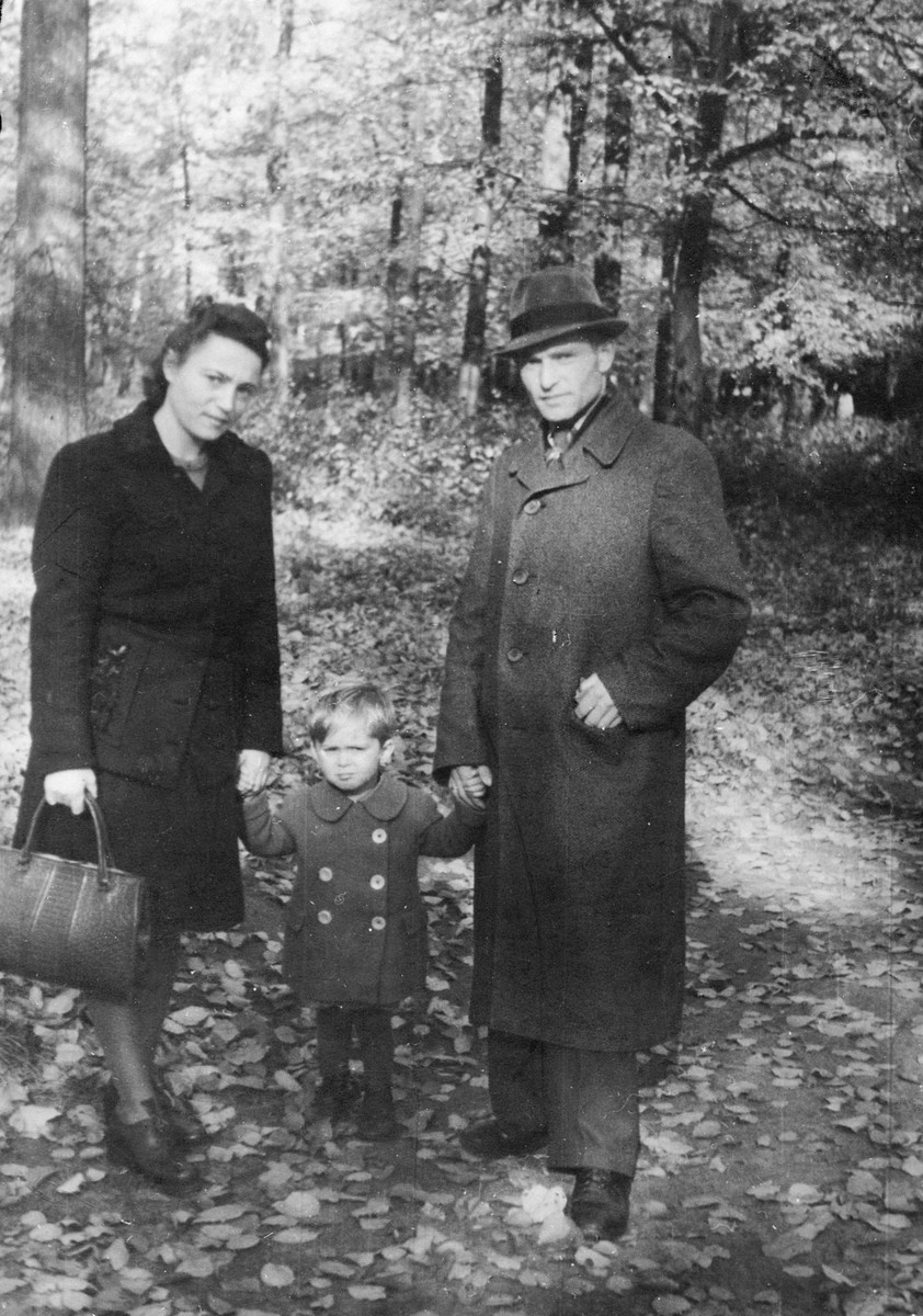 A young Jewish toddler who had survived in hiding holds hands with his aunt and father.  Pictured are Lifcia Najman, Heskel Zilbersztok and Herszl Heniek Zilbersztok.  Heskel was born in 1942 and hidden with a Polish Catholic family.  Lifcia helped her brother-in-law locate the boy and claim him after the war.