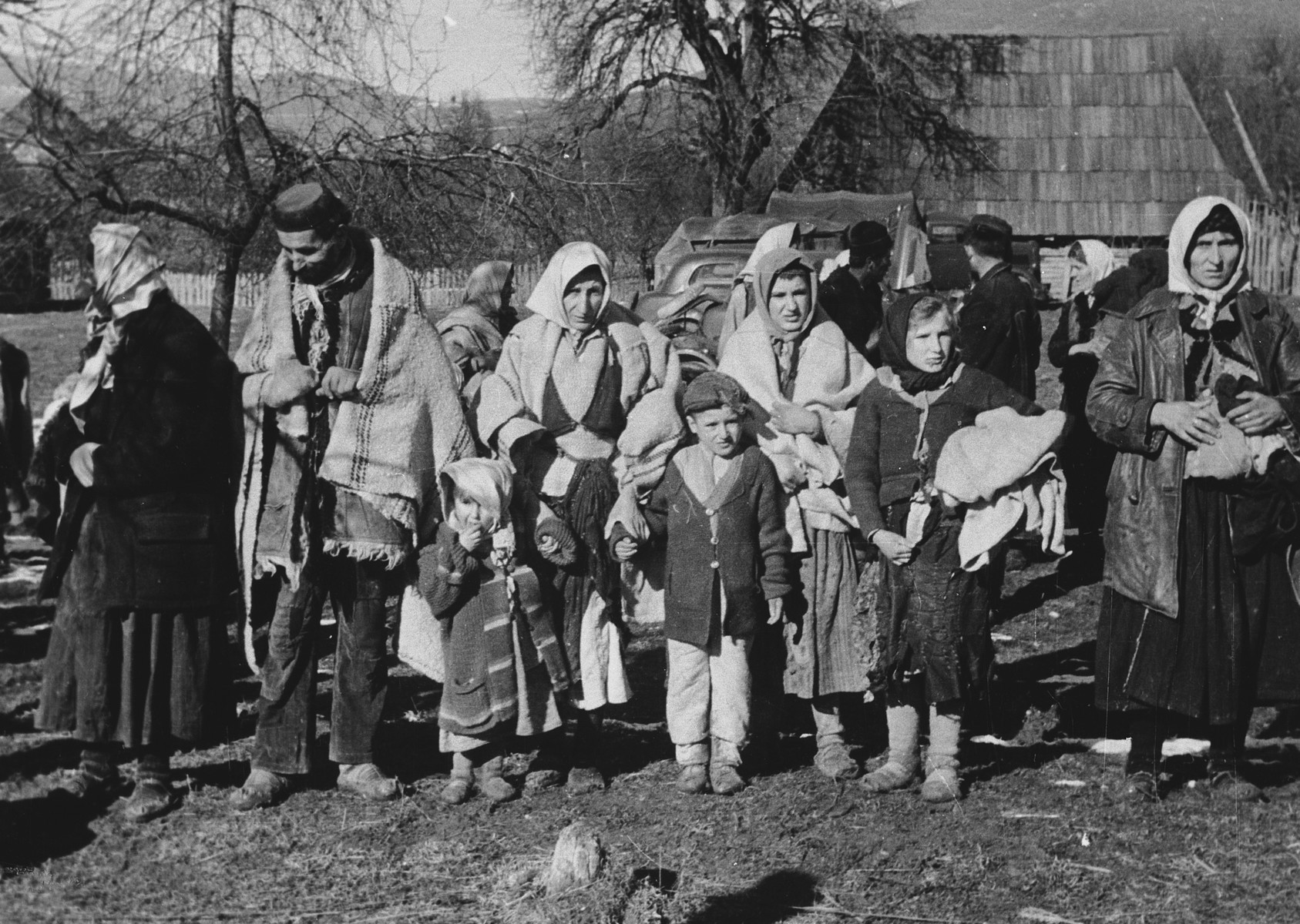 "Group portrait of refugees in Croatia standing outside a wooden farmhouse.  Original caption reads: ""The population, who was driven forcibly by partisans, returns to its home after wandering unkempt and starved in the forests for days.""  This is one of a collection of photographs from Friedrich Wilhelm Krueger, commander of the ""Prinz Eugen"" Division."