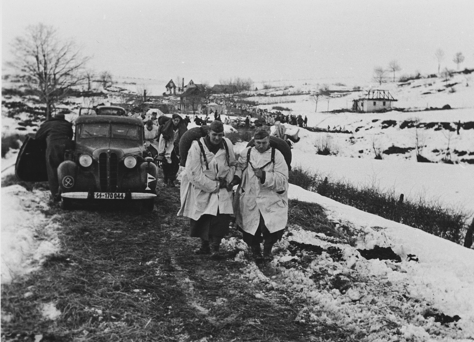 "Members of the ""Prinz Eugen"" Division march down a road near the town of Grahovo, Croatia.  The original caption reads: ""Tanks are brought into action against the enemy in Grahowo.""  This is one of a collection of photographs from Friedrich Wilhelm Krueger, commander of the ""Prinz Eugen"" Division."