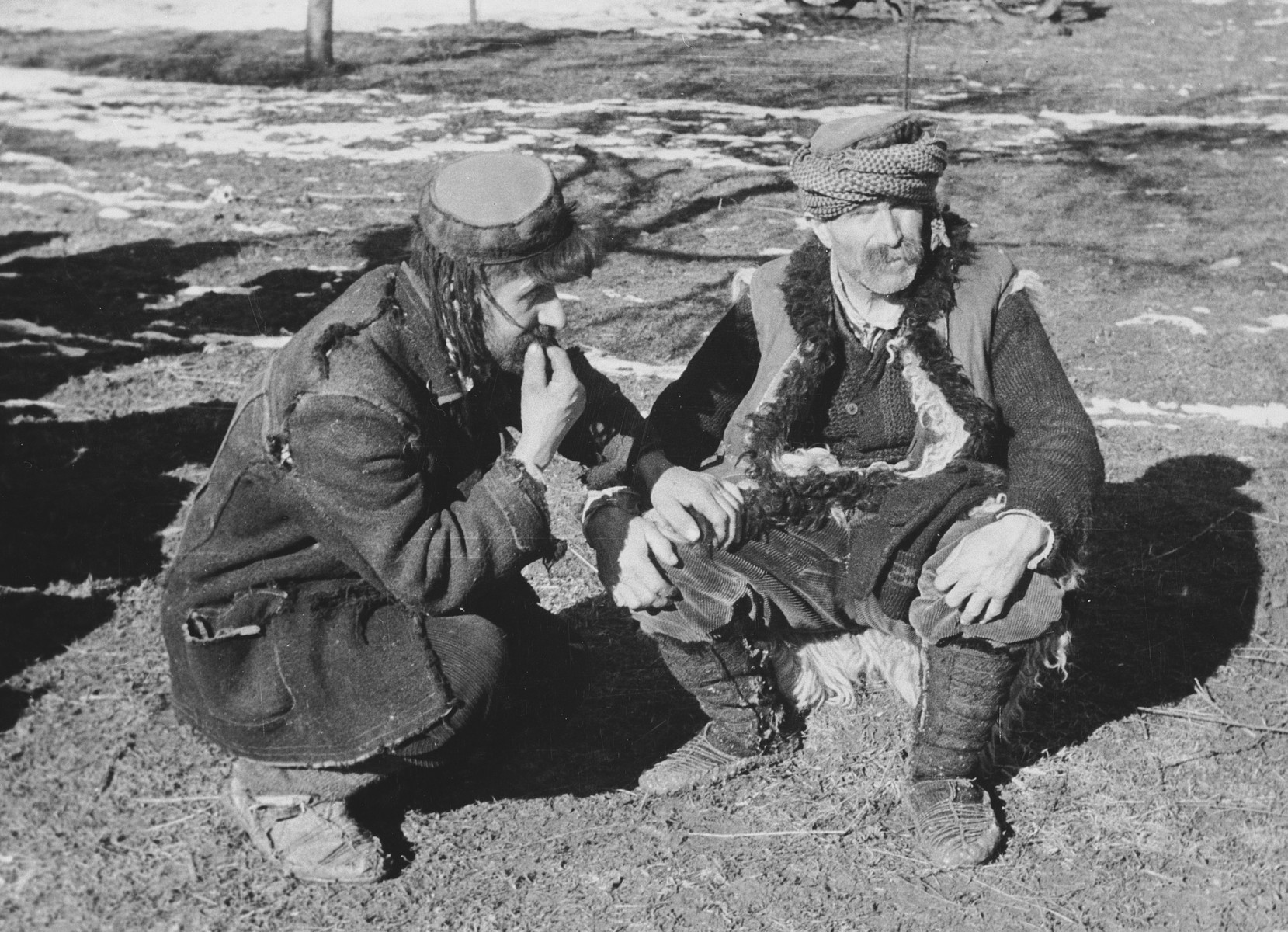 """Two refugees from Petrowatz sit by the side of the road.  Original caption reads:  """"Local people from the area of Petrowatz.""""  This is one of a collection of photographs from Friedrich Wilhelm Krueger, commander of the """"Prinz Eugen"""" Division."""