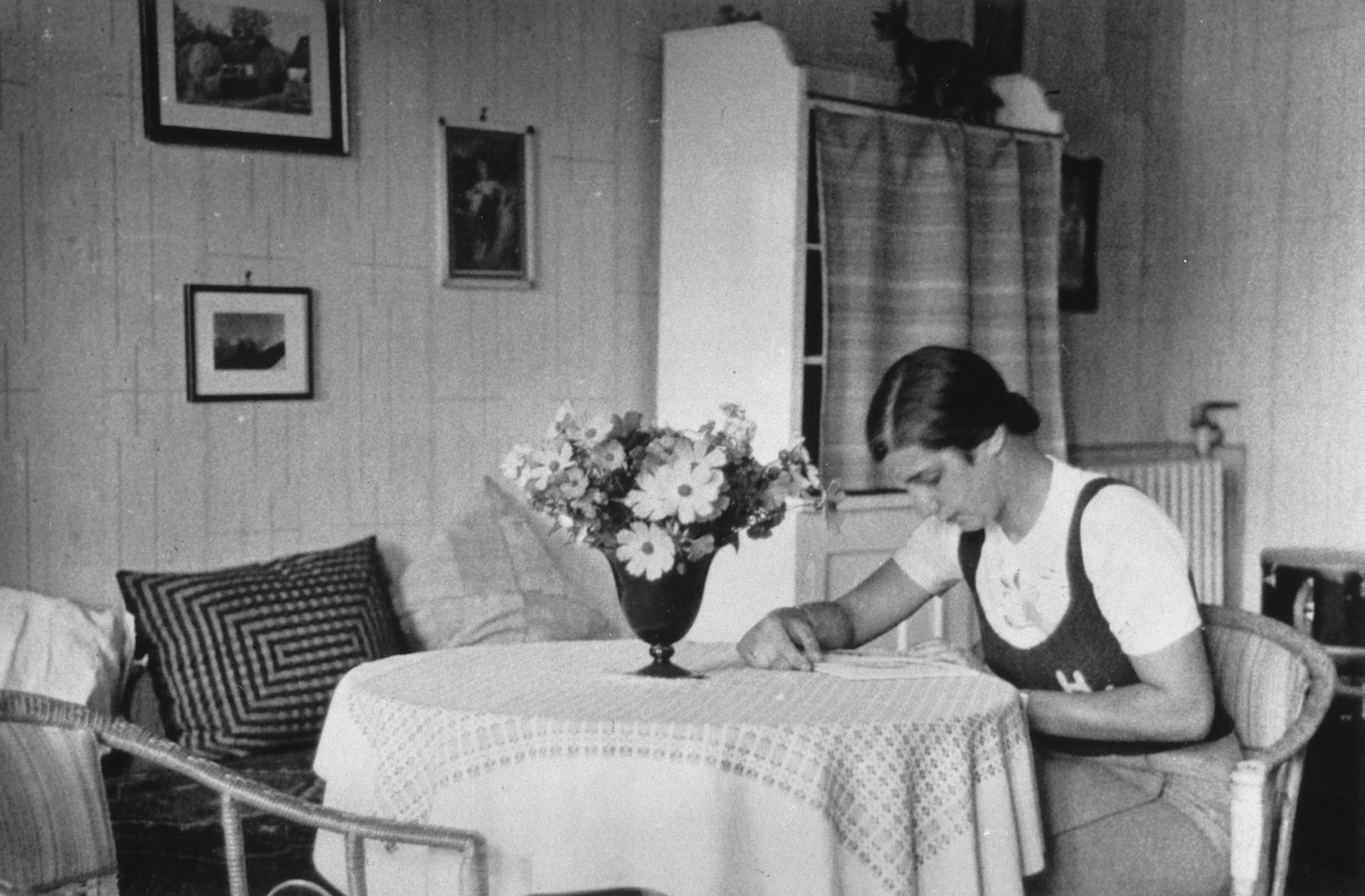 A German-Jewish teenage girl sits at a table in her home and reads.   Pictured is Hildegard Wolff.