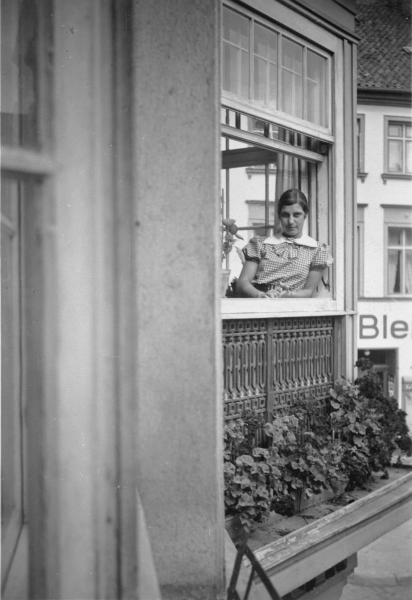 A German-Jewish teenage girl looks out the window of her home.  Pictured is Hildegard Wolff.
