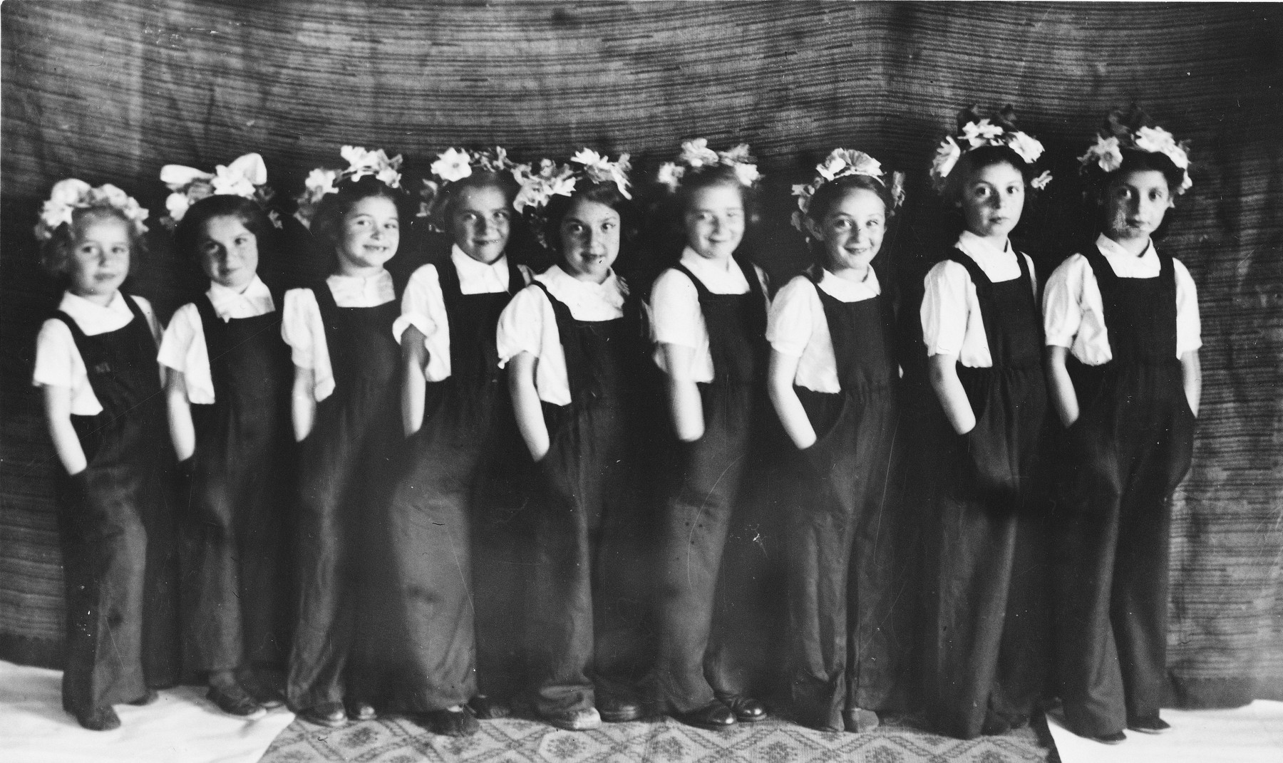 Young girls, dressed in overalls and with flowers in their hair, put on a school performance at the Novaky labor camp.  Among those pictured are Mira Frenkel (third from right) and twin sisters (first and second from the right).