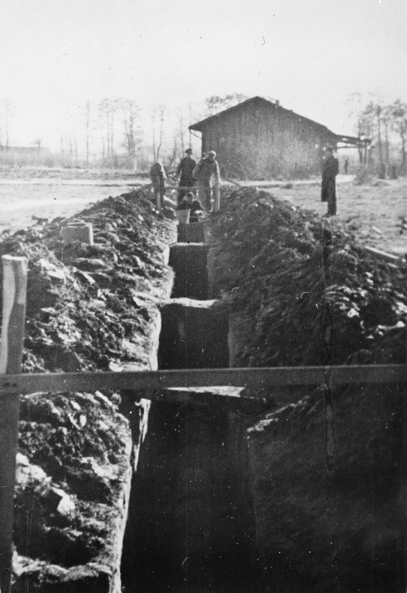 Prisoners from the Sixth Labor Battalion work on the latrine plumbing system at a Slovak labor camp.