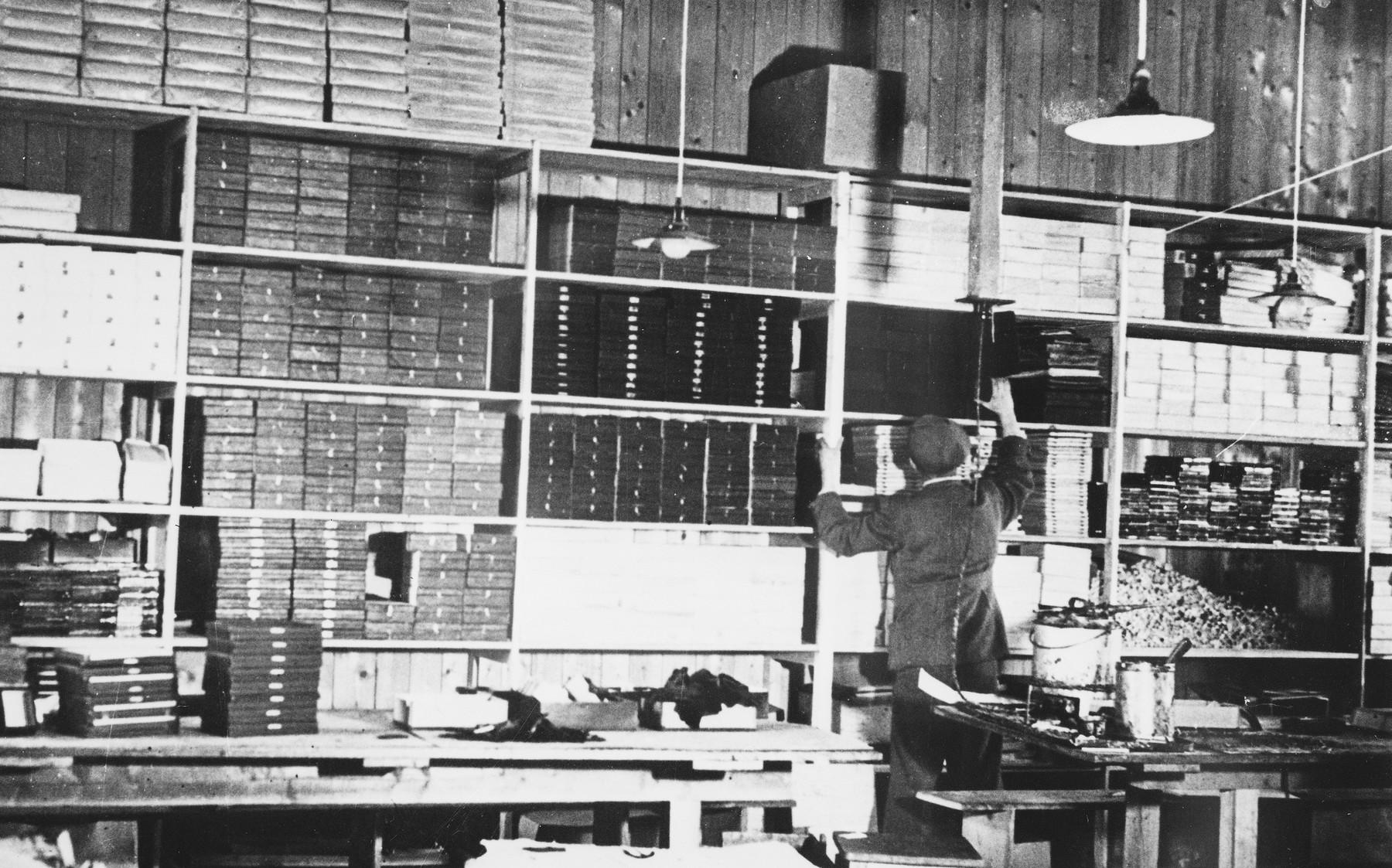 A prisoner shelves boxes at a Slovak labor camp.