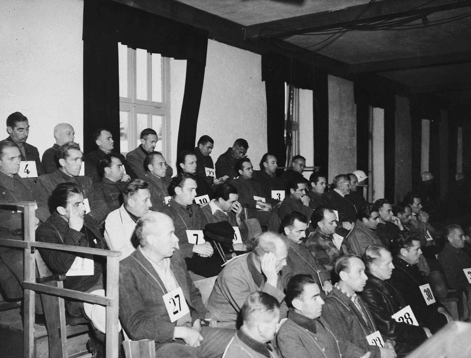 View of the defendants in the Dachau trial wearing identifying number tags seated in the dock.
