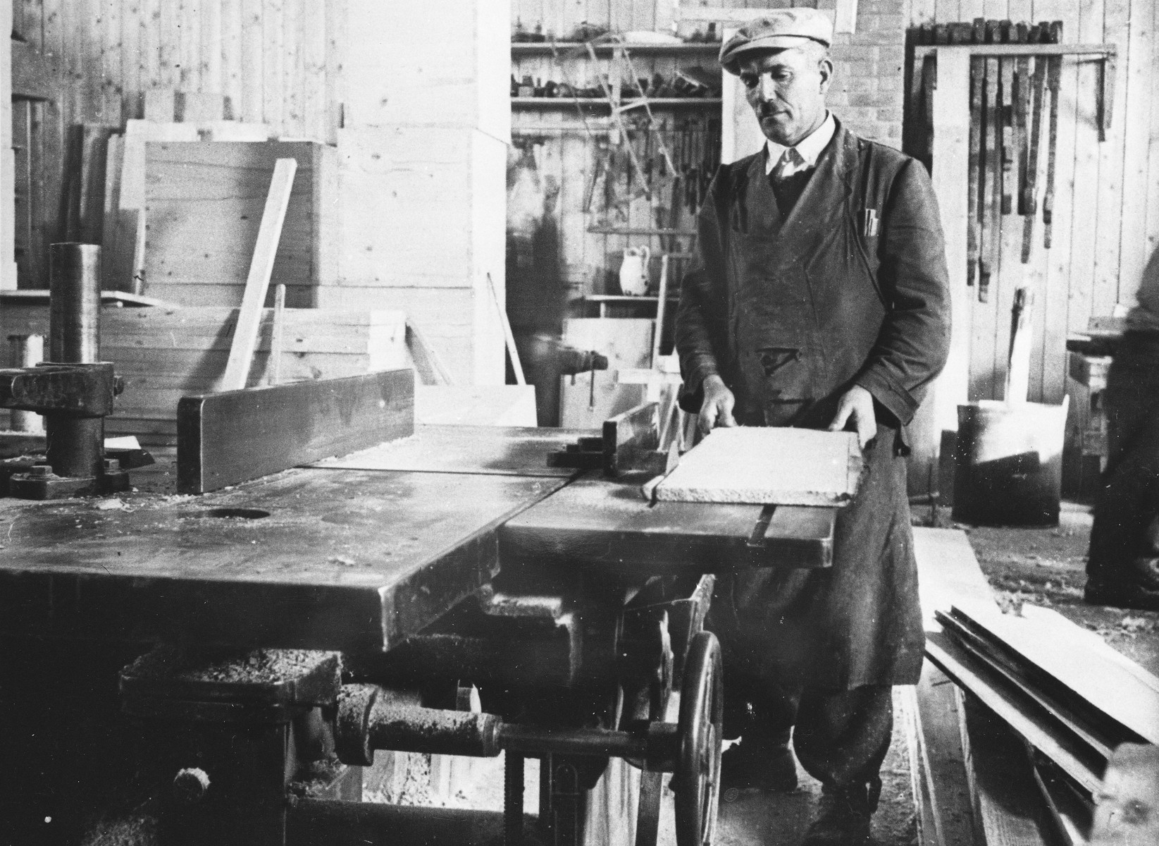 A man saws wood in a workshop at a Slovak labor camp.