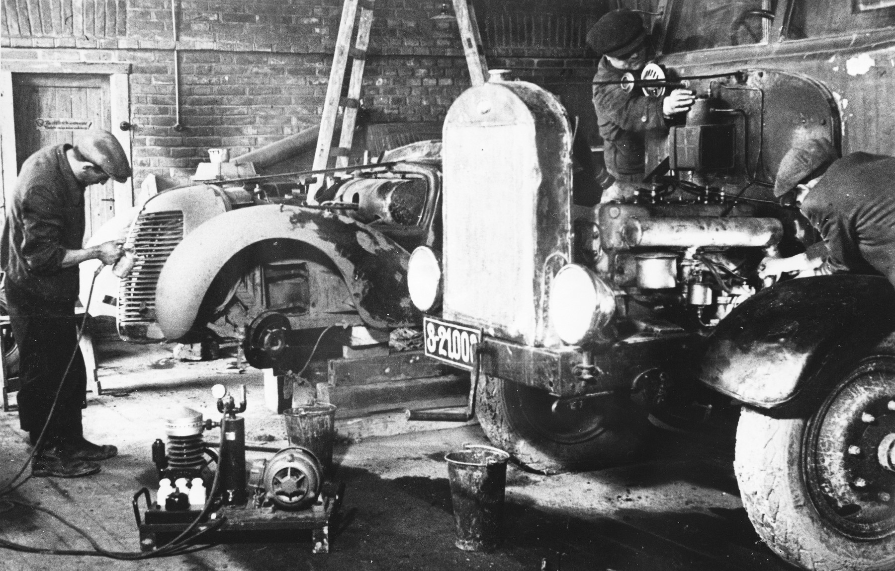 Prisoners repair automobile engines at a Slovak labor camp.