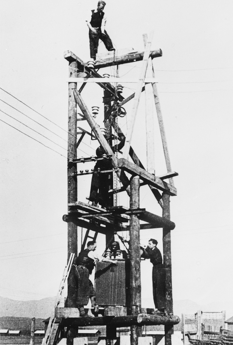 Prisoners from the Sixth Labor Battalion construct a guard tower at a Slovak labor camp.