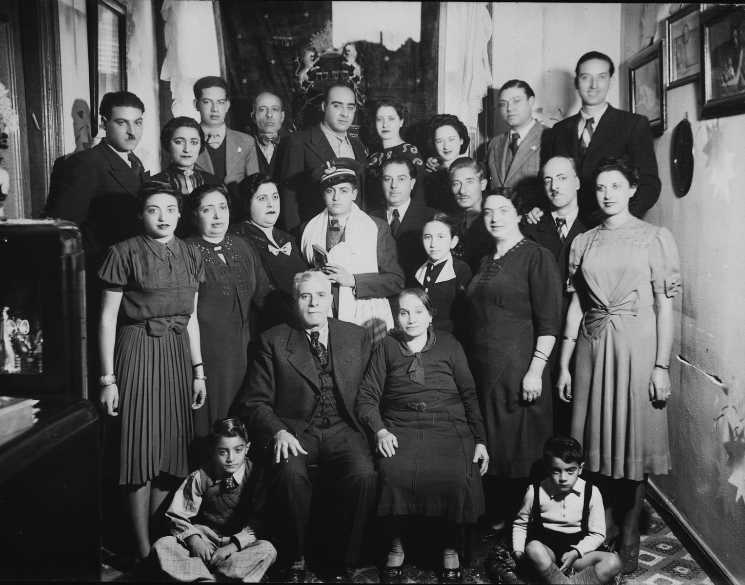 A Greek Jewish family gathers for a group portrait surrounding a bar mitzvah boy clad in a tallit.  Pictured are the Menashe family.  Of all those pictured, only three survived: Sylvia Amar (second row, far right), Nissim Menashe (top row, far right) and Oro Menashe (top row, center).