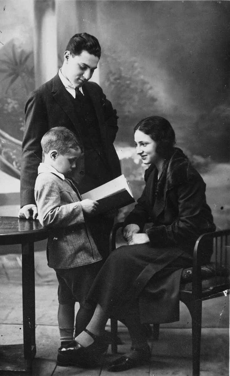 Studio portrait of a Greek-Jewish family; the parents look on as their son reads a book.