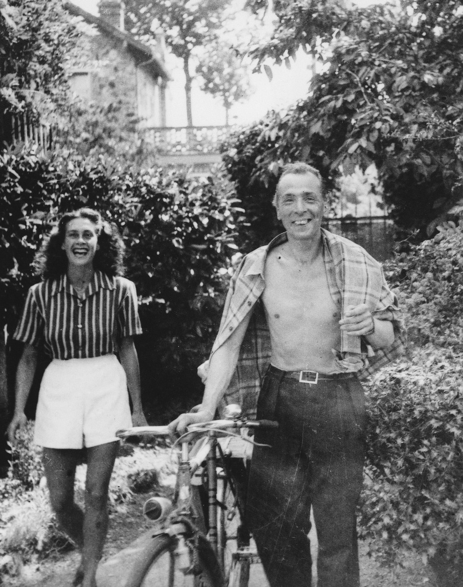 A Jewish dancer in hiding walks down a tree lined path with an unidentified man.  Pictured on the left is Sadie Rigal.