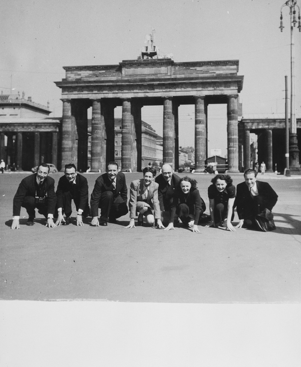A company of French singers and dancers poses in front of the Brandenburg Gate while on a performance tour in Germany.  Sadie Rigal, who is actually a Jew in hiding, is pictured in the center.  On the far left is her dance partner, Frederic Apcar.  Edith Piaf is show third from the right.
