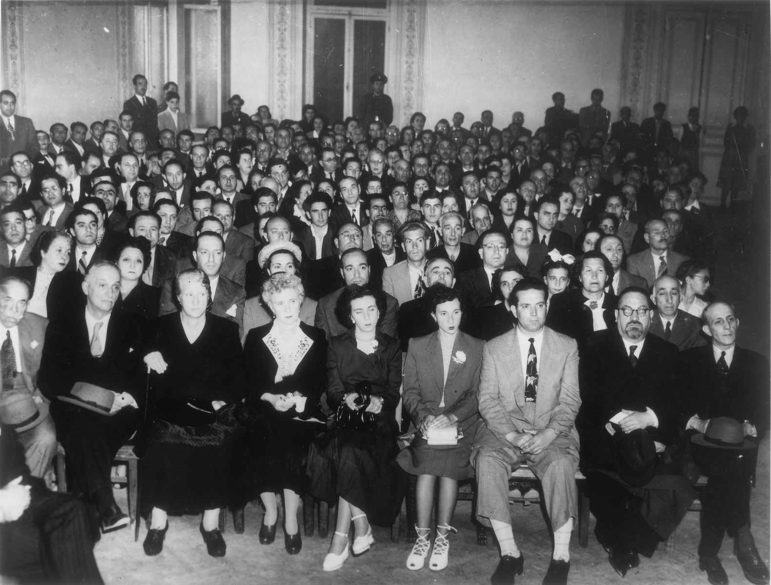 A large crowd assembles in the Parnassos lecture hall in Athens to celebrate the founding of Israel.    Rabbi Elias Barzilai is seated in the front row, second from the right.  Jack Amar is seated on the far right.  Also pictured are Noah Yeshouroun, Sylvia Levy, Freddy Barouh, Rosetta Vital, Noulis Vital, Elias Leon, Markos Tabach, Michael Matsas, Pepo Benouziglio, Lydia Shabetay, and Kaimis.