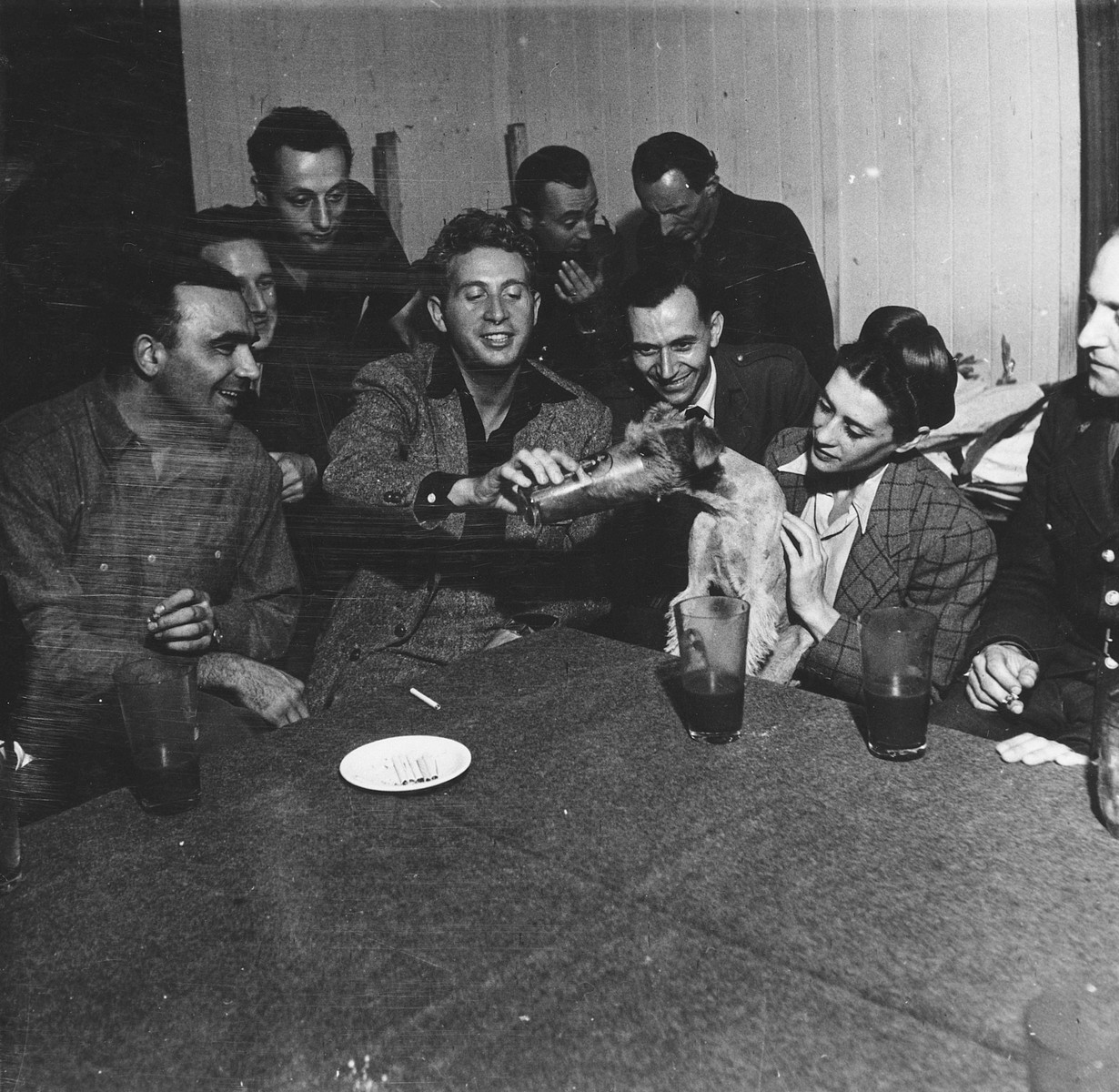 A group of French performers feeds beer to a dog while on tour in Germany.  Sadie Rigal, who is actually a Jew in hiding, is on the right.  Also pictured is the French singer, Charles Trenet, holding the glass in the middle.  [Maurice Chevalier who also toured with them may also be in the photograph.]