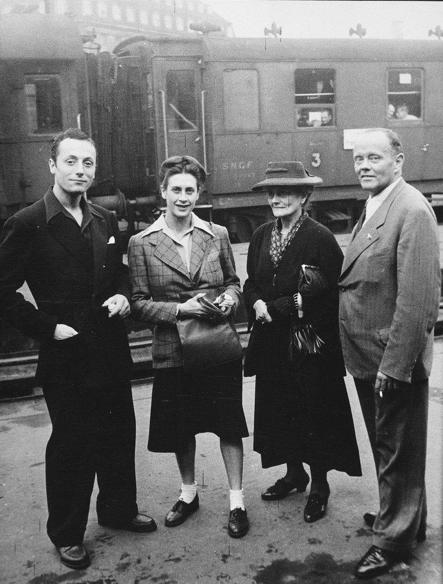 Two French dancers pose on a train platform while on a performance tour in Germany.  Sadie Rigal [second from the left], is actually a Jew in hiding.  The man on the far left is her dance partner, Frederic Apcar. [It is unclear whether this photograph was taken in France or Berlin.]