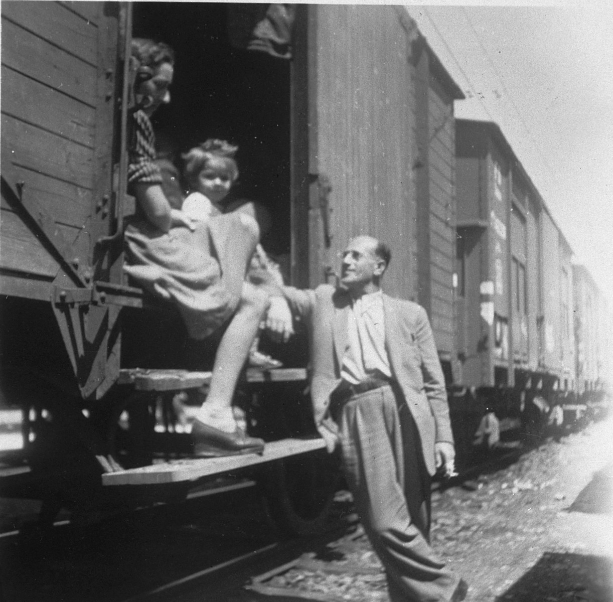 A Polish Jewish family poses by the entrance to a cattle car as they prepare to leave Hungary for the west.  Pictured are Mania and Jeanine Ament.  [The man may be Yona Stern.]