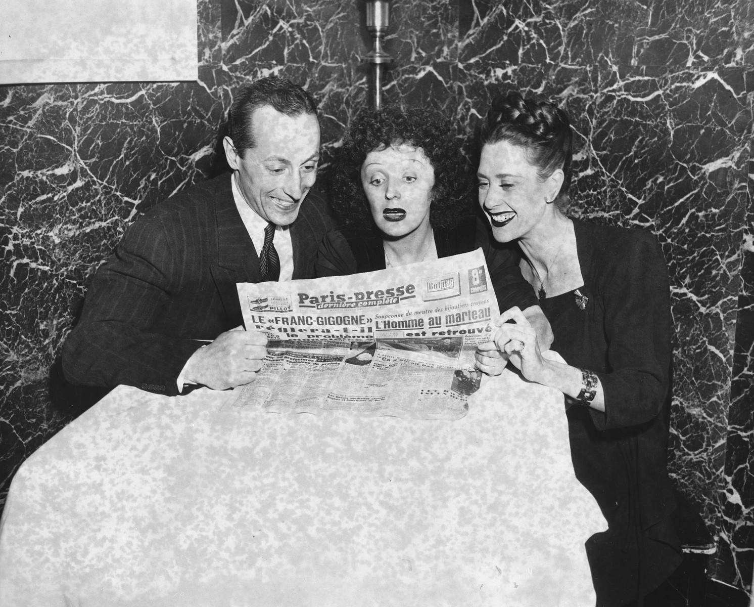 Three French singers and dancers huddle around an open French newspaper.  Sadie Rigal, who is actually a Jew in hiding, is pictured on the right.  On the left is her dance partner, Frederic Apcar.  Edith Piaf is in the center.