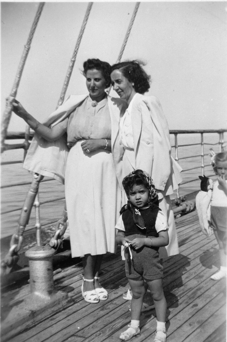A Greek Jewish family stands on board a ship.