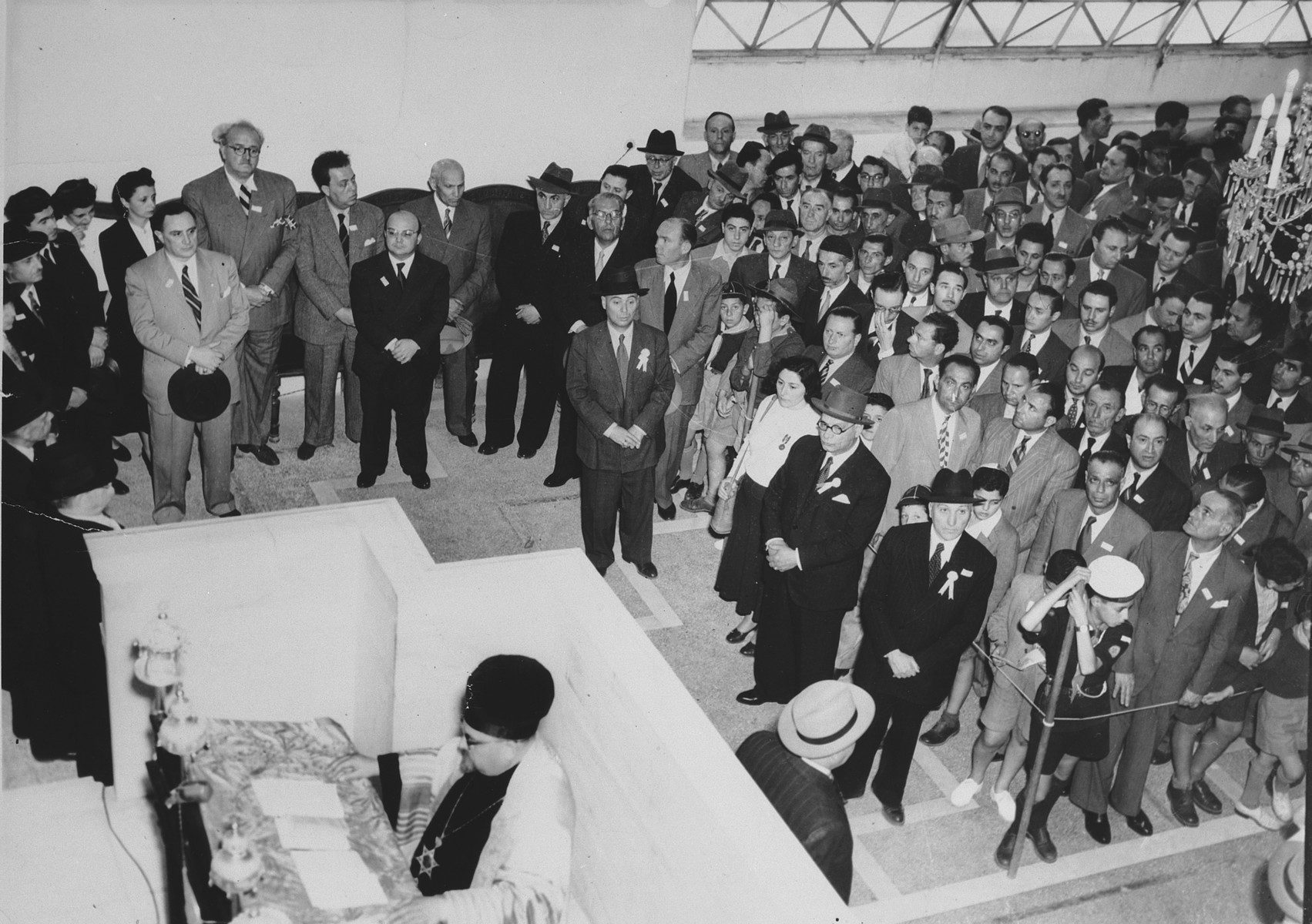 A large crowd assembles in the synagogue in Athens to celebrate the founding of Israel.  Rabbi Elias Barzilai leads the service.  Also pictured are Asher Moissis (attorney and President of the Central Board of Jewish Communities), Rabbi Mizrahi of Corfu, Kostas Kotzias (Mayor of Athens), Dimitri Avramopoulos (diplomat and member of parliament),  Lavinger (Presient of Central Board of Jewish Communities), Jacques Beraha, ? Moshe, ? Ouziel, Sam Natan, Sam Levy and Simtov Hassid.