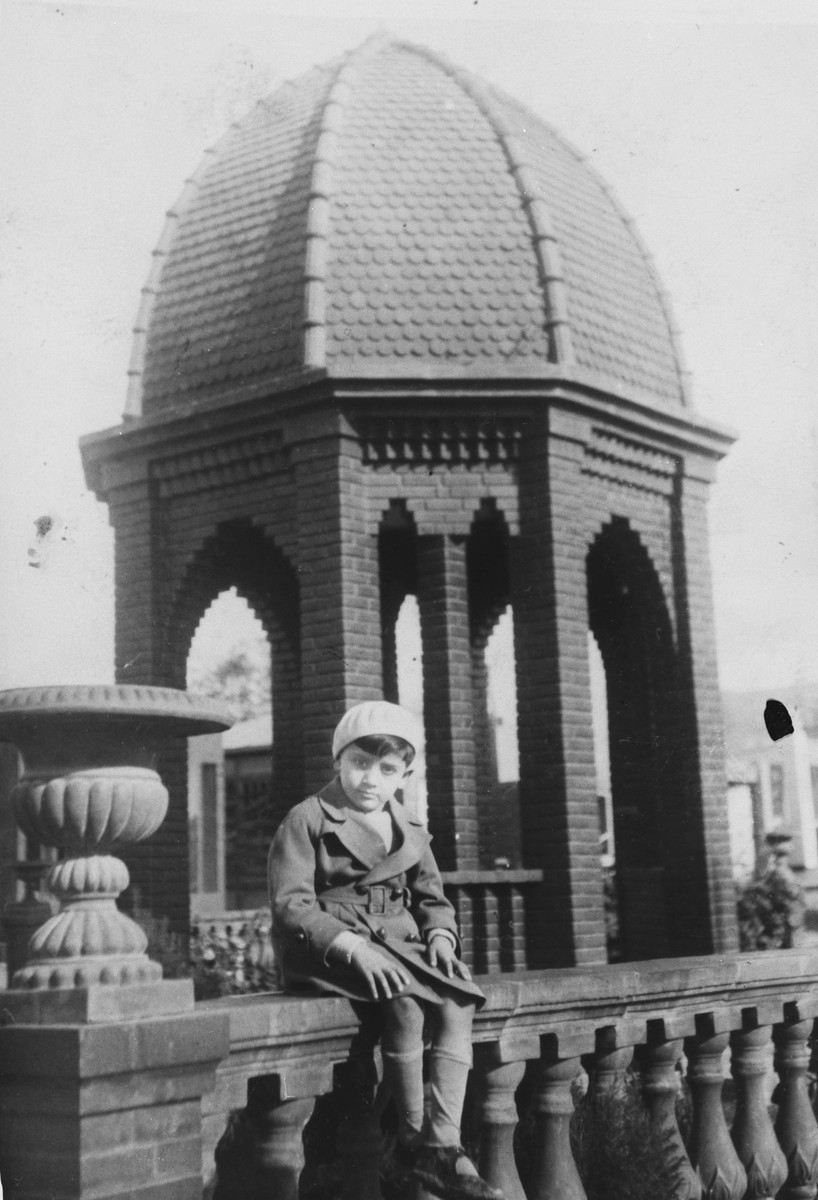 Close-up portrait of a young Greek-Jewish boy sitting on a railing in front of a dome.