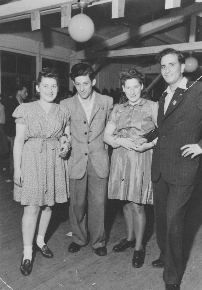 Two couples pose together at a party in the Zeilsheim displaced person's camp.  Chuna Grynbaum is standing on the far right.