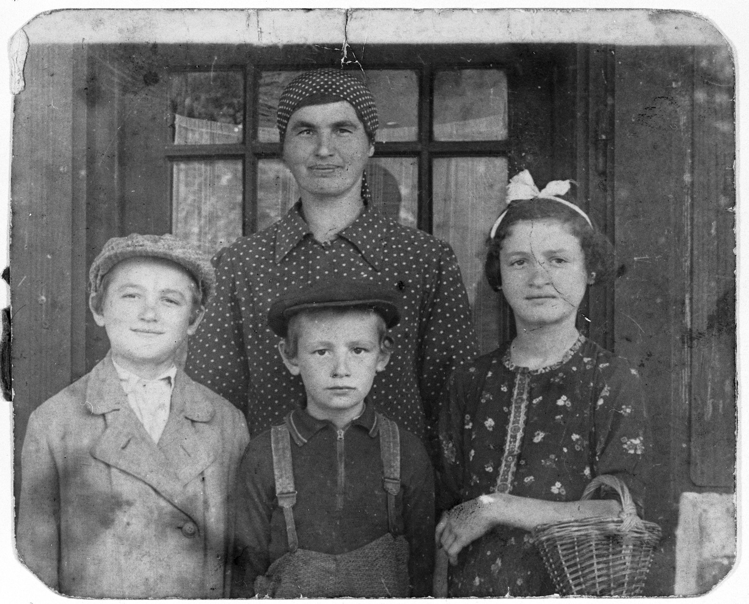 A religious Hungarian Jewish woman poses with her three youngest children.  Pictured are Rosi Zelmonovits (back) and her children (left to right) Moritz, Volwi and Eva.