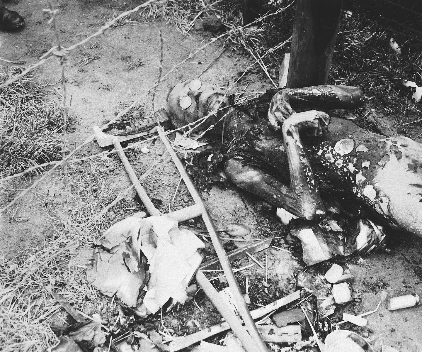 View of a badly burned corpse lying next to a barbed wire fence in the Leipzig-Thekla sub-camp.  The man's glasses are still on him and a crutch lies next to him.