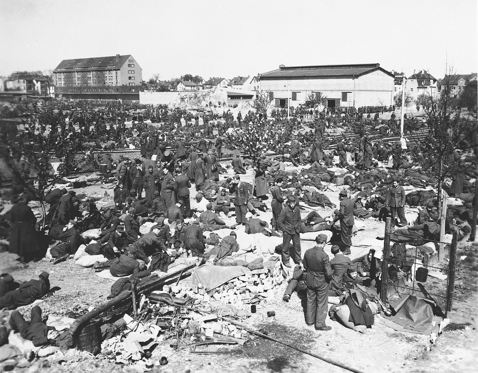 German POWs crowd into a large public square covered with rubble.