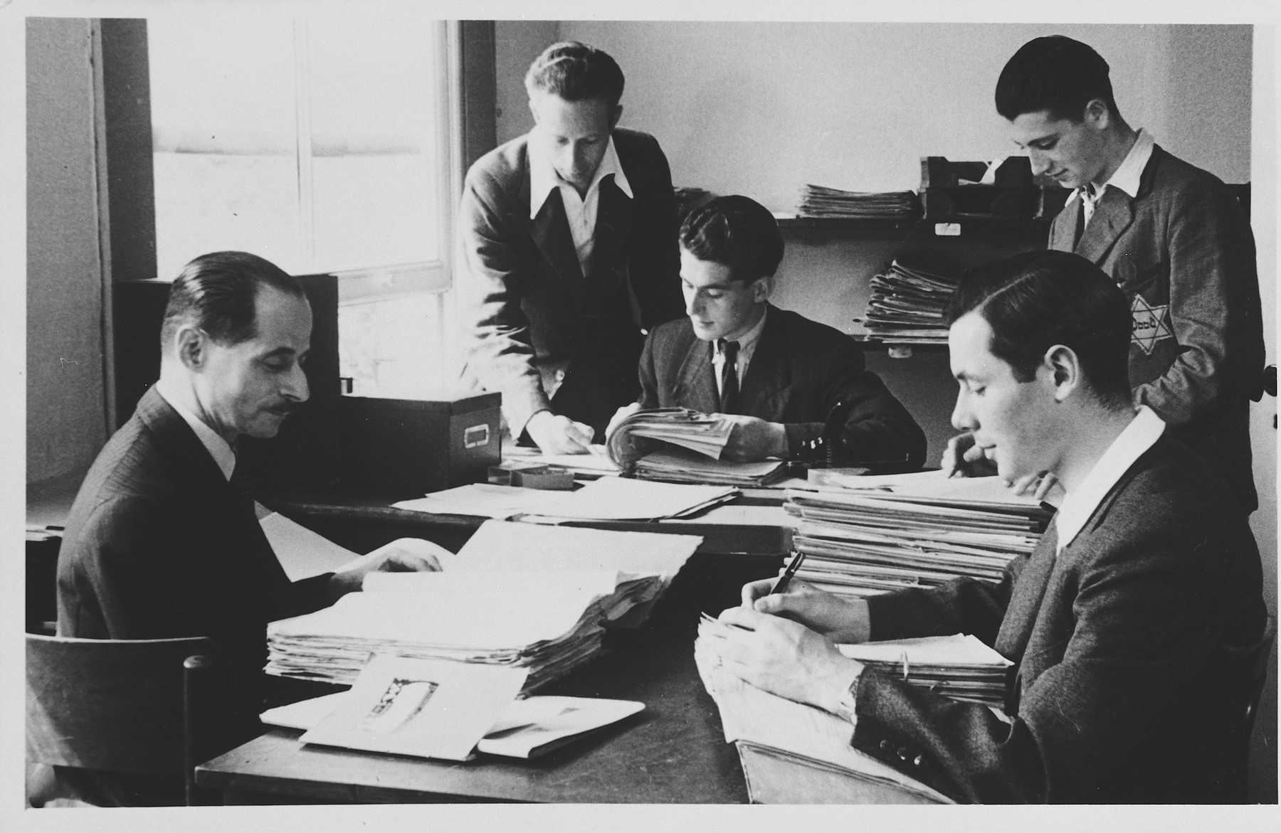 Dutch Jews, some wearing Jewish Stars, work in the newspaper office.  Pictured on the far left is Kurt Zielenziger.
