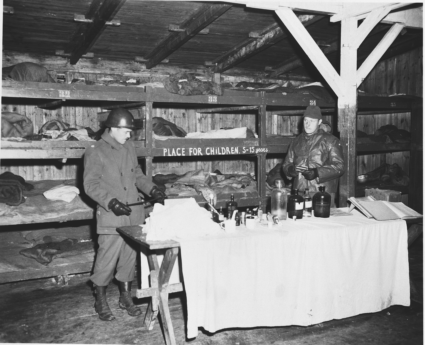 "An American soldier looks at items on a display table inside a barracks in the Buchenwald concentration camp.  ""Place for children 5-15 years"" is written on the side of one of the bunks."