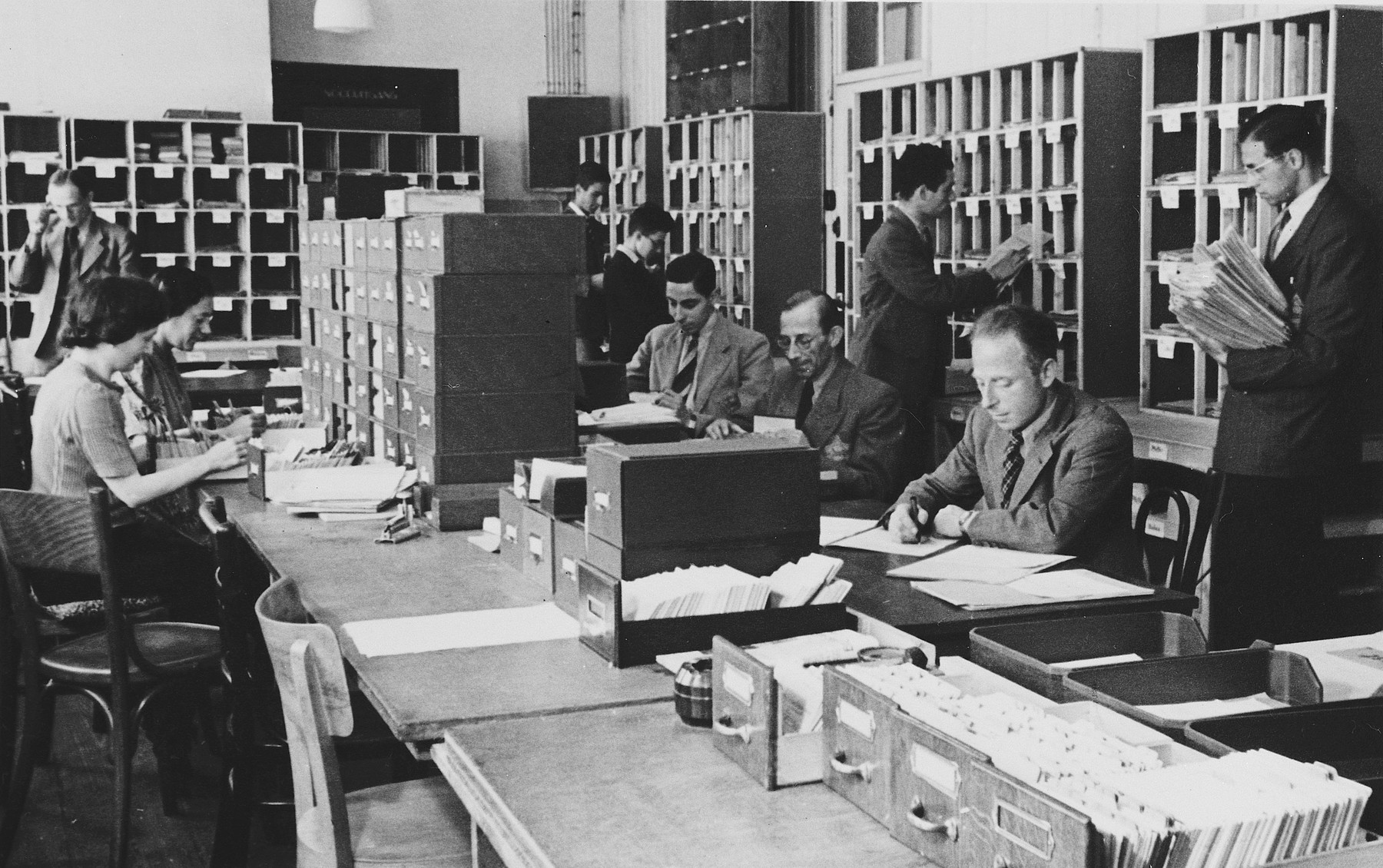 Workers sort and file papers and cards in the offices of the Joodse Raad in Amsterdam.