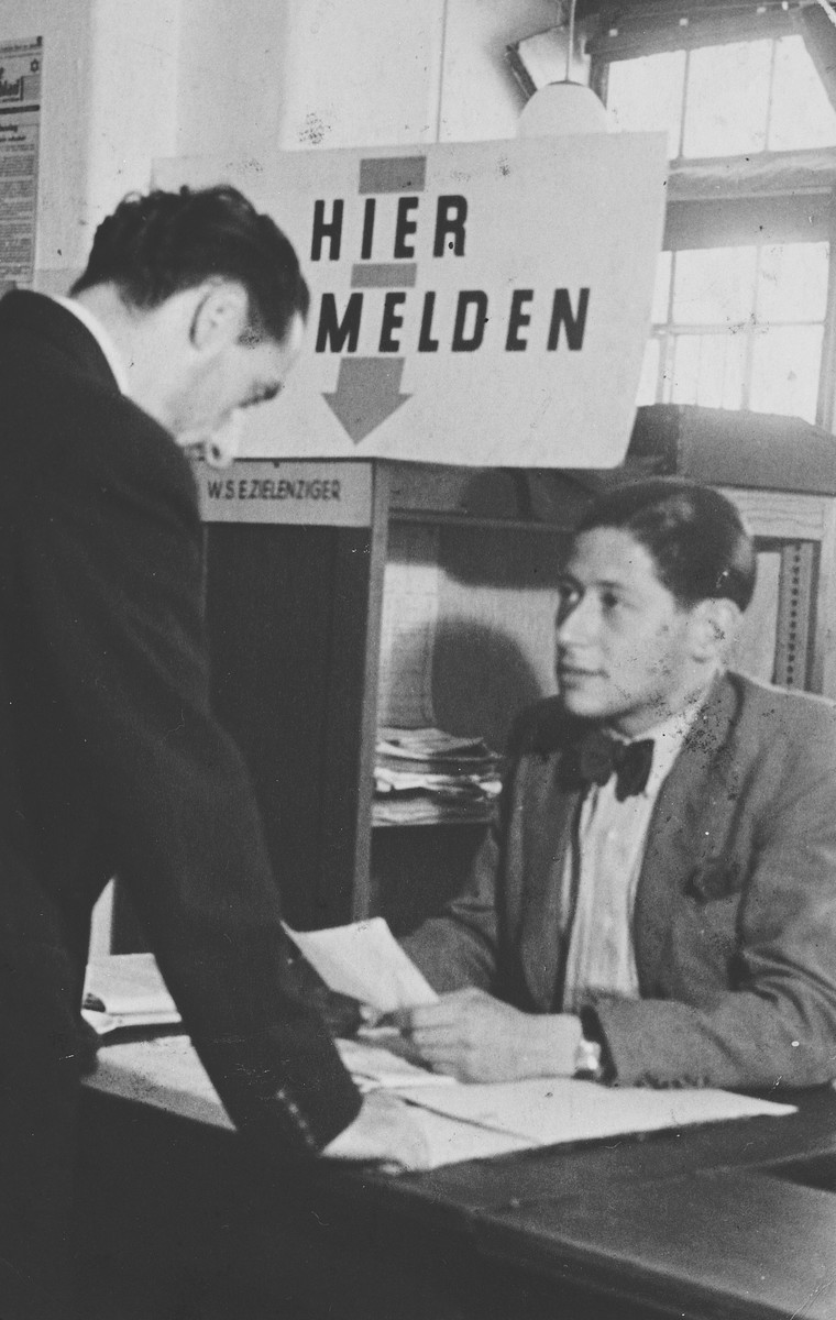 A Dutch Jew seeks assistance from the emigration department of the Joodse Raad (Jewish Council) in Amsterdam.  Seated behind the desk is Erich Zielenziger.