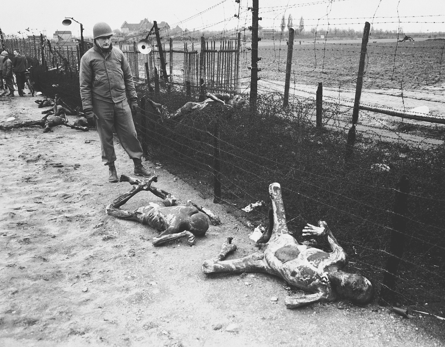 An American soldier stares at two badly burned corpses lying next to a barbed wire fence in the Leipzig-Thekla sub-camp.