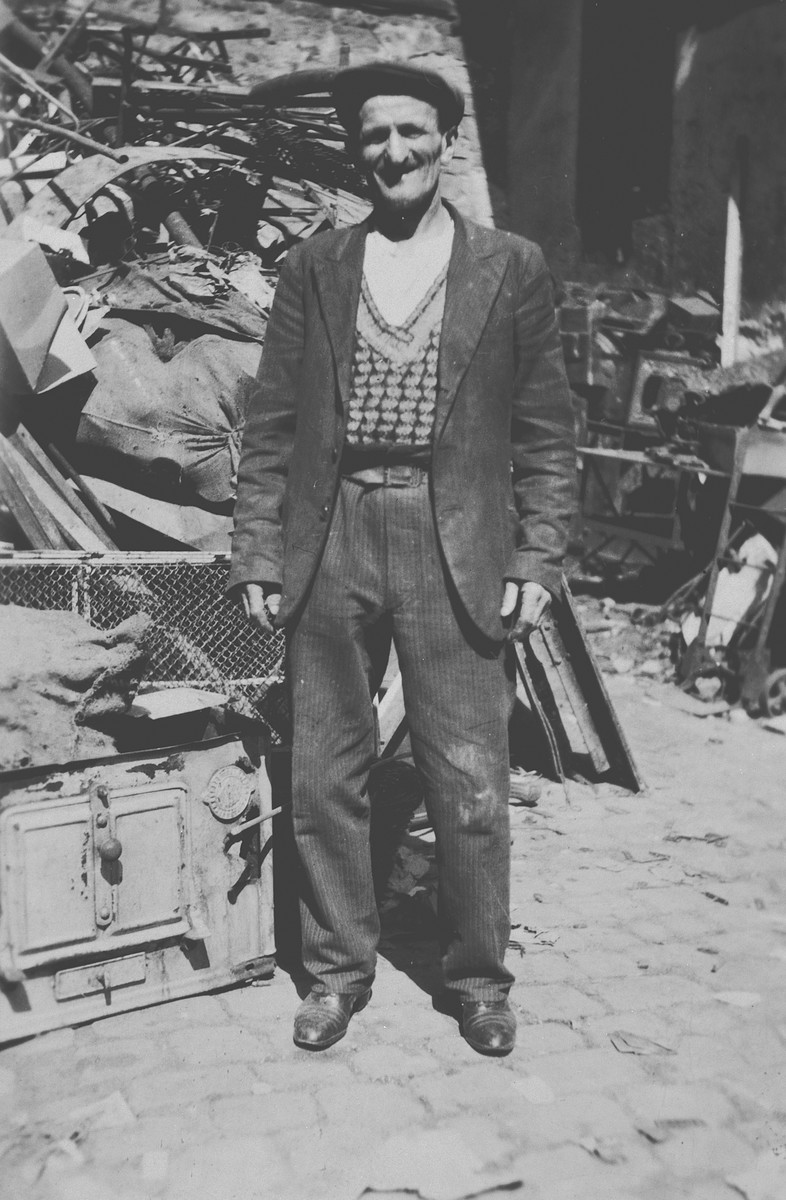 A Deaf and mute Jewish man poses in front of a pile of discarded scrap metal.  Pictured is Moshe Aron Spielman (great-uncle of the donor).  He lived with the donor's immediate family in the Krakow ghetto until 1942 when he was rounded-up and deported to Belzec where he perished.
