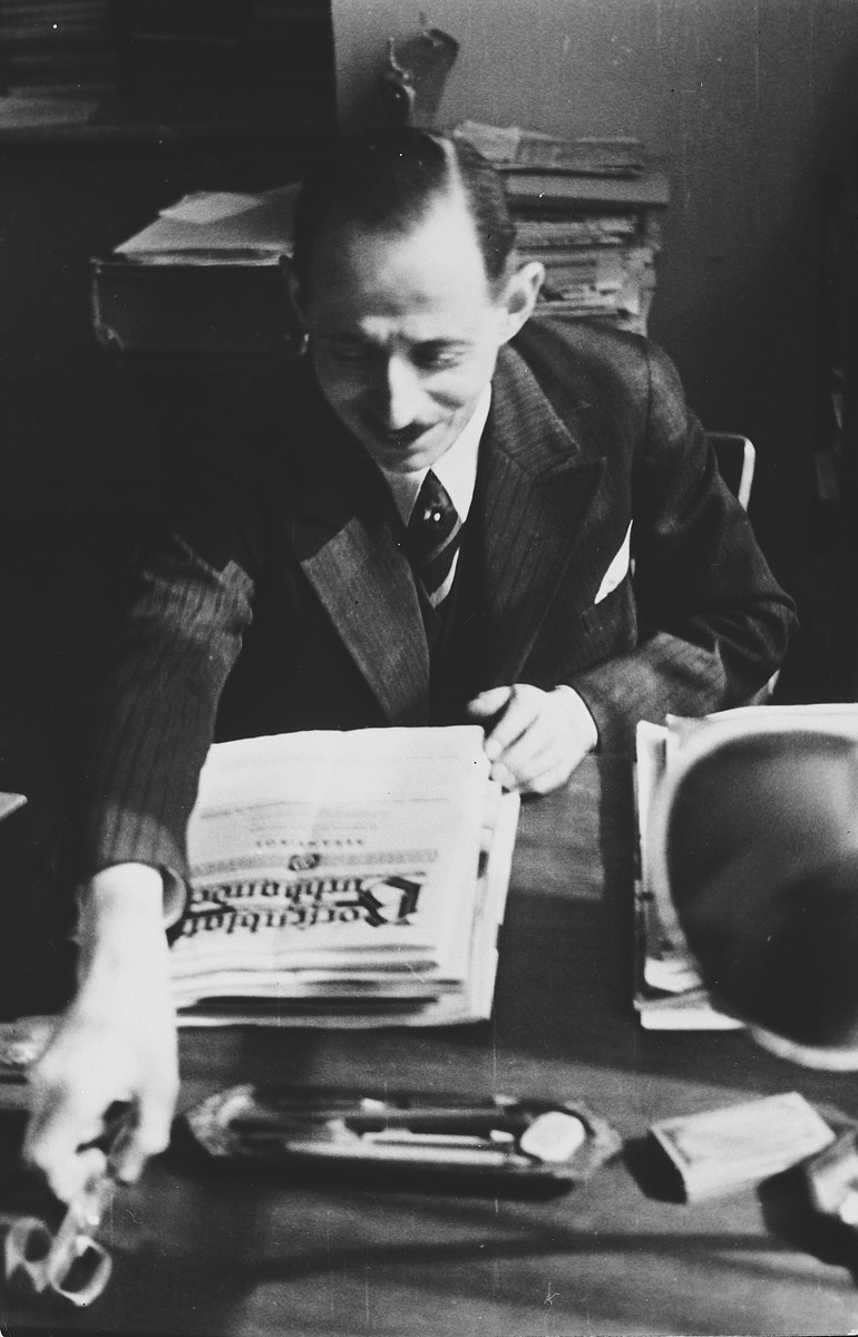 Portrait of a German-Jewish immigrant sitting at his desk reading a newspaper.  Pictured is the journalist, Kurt Zielenziger.